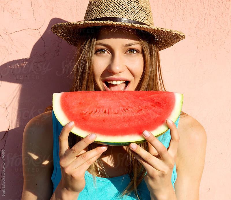 beautiful woman eating watermelon by Sonja Lekovic for Stocksy United