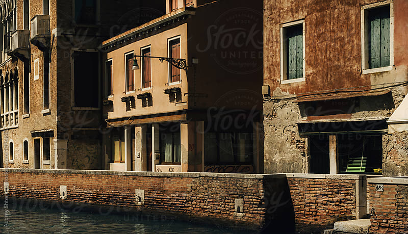 Old rustic mediterranean houses and shops with canal at old quarter/neighborhood.Italy. by Audrey Shtecinjo for Stocksy United