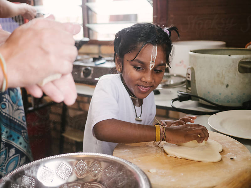 Joyful indian girl learning how to prepare dough by Martin Matej for Stocksy United