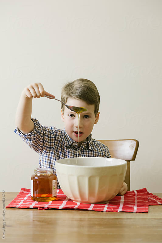 Boy adds ingredients to bowl while baking by Kirsty Begg for Stocksy United