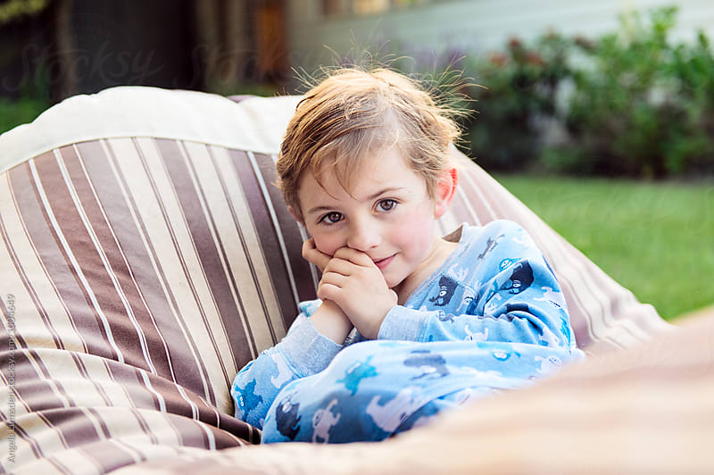 Portrait of a small boy in pajamas in a garden in the evening by Angela Lumsden for Stocksy United