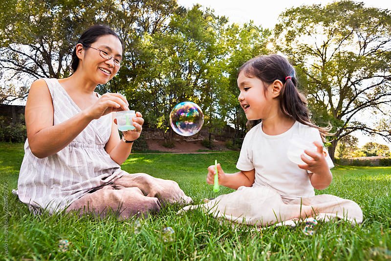 Asian mother and daughter with soap bubbles by yuko hirao for Stocksy United
