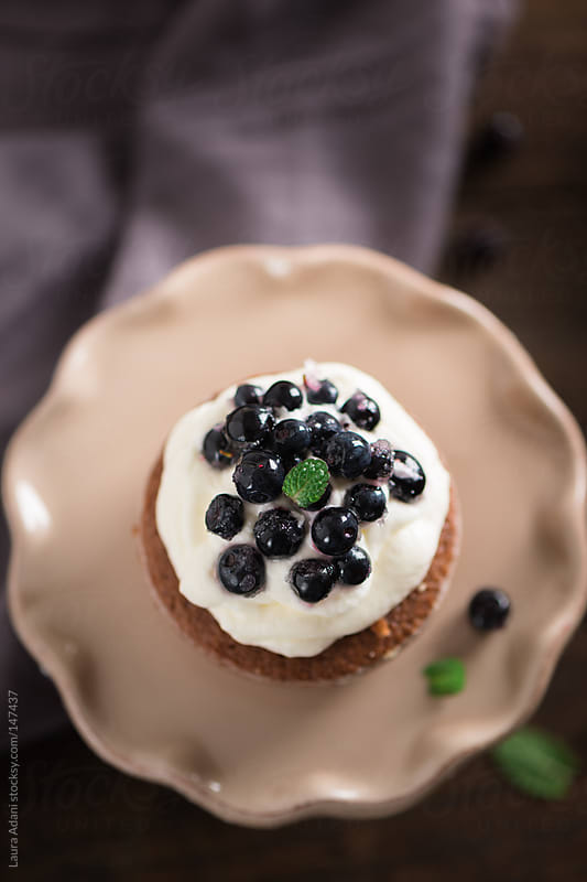 mini chocolate cake with cream and blueberries by Laura Adani for Stocksy United