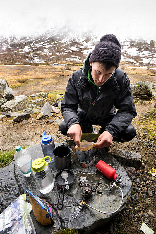 Man making dinner in the backcountry by Tristan Kwant for Stocksy United