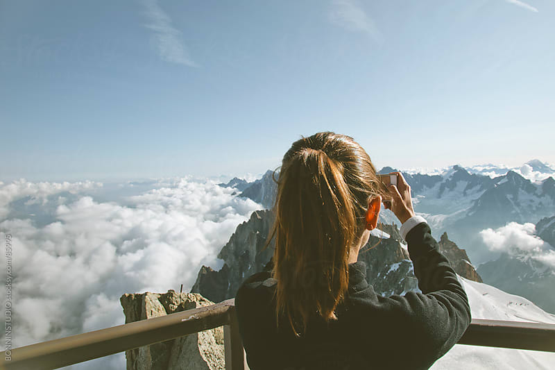 Mountaineer woman taking photos of the Alps landscape. Chamonix, France. by BONNINSTUDIO for Stocksy United