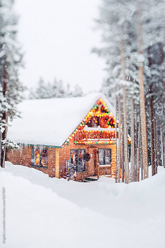 Gingerbread cabin glows with holiday lights amongst banks of snow in a mountain forest by Angela Lumsden for Stocksy United