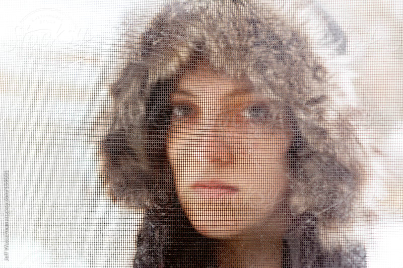 Portrait of Attractive Young Woman in Winter Through Screen in Winter by Jeff Wasserman for Stocksy United