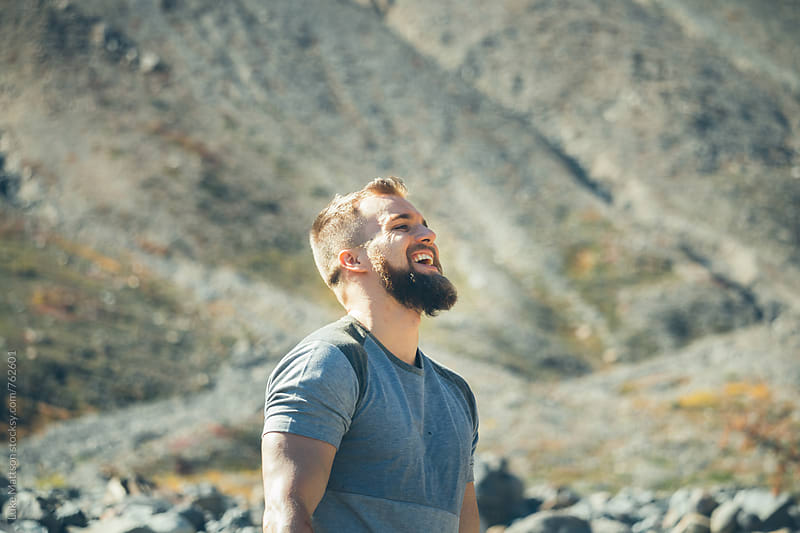 Bearded Blond Man Laughing In Rocky Riverbed While On A Hike by Luke Mattson for Stocksy United