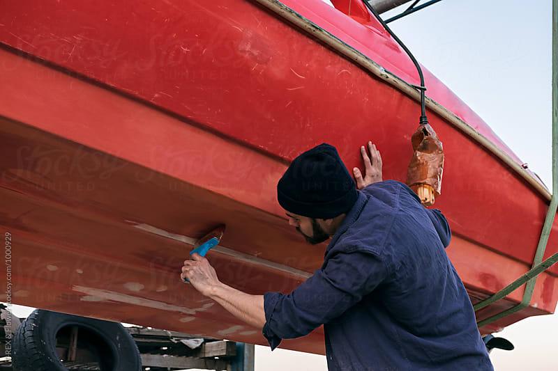 Man restoring red boat by Danil Nevsky for Stocksy United