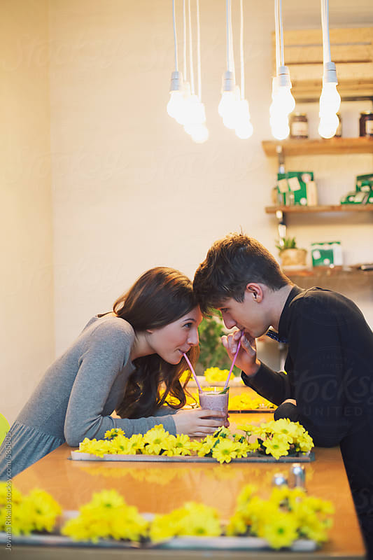 Happy couple drinking smoothie in a coffee bar by Jovana Rikalo for Stocksy United