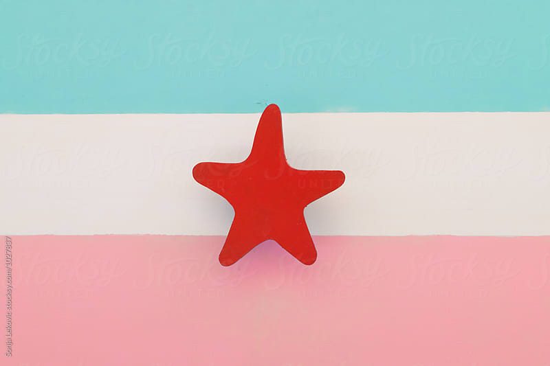 pastel pink and blue flag design with a red star by Sonja Lekovic for Stocksy United