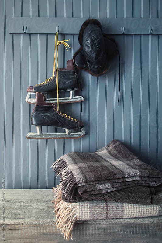 Men's vintage skates and hat hanging on hook  by Sandra Cunningham for Stocksy United