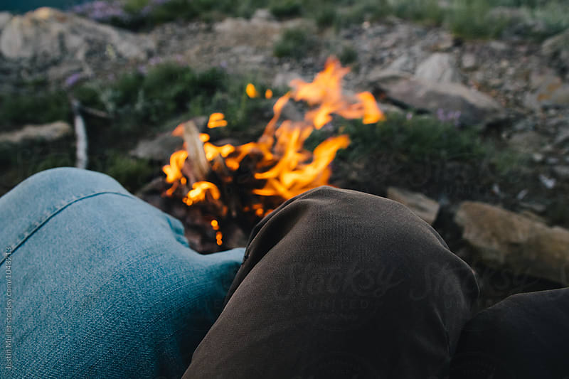Cozy young couple sitting at a campfire by Justin Mullet for Stocksy United