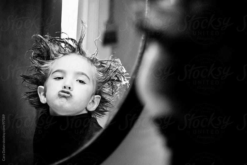 Boy with messy, spiked up hair makes a silly face in the bathroom mirror  by Cara Dolan for Stocksy United