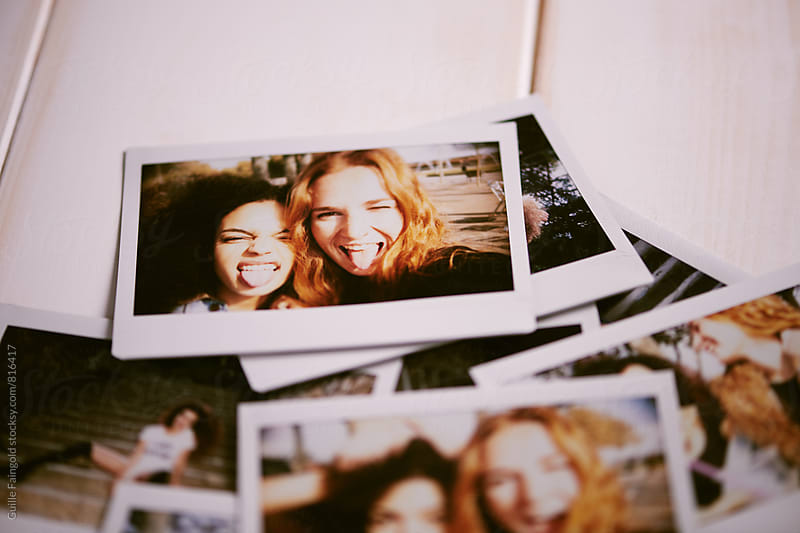 Heap of instant photos lying on table by Guille Faingold for Stocksy United