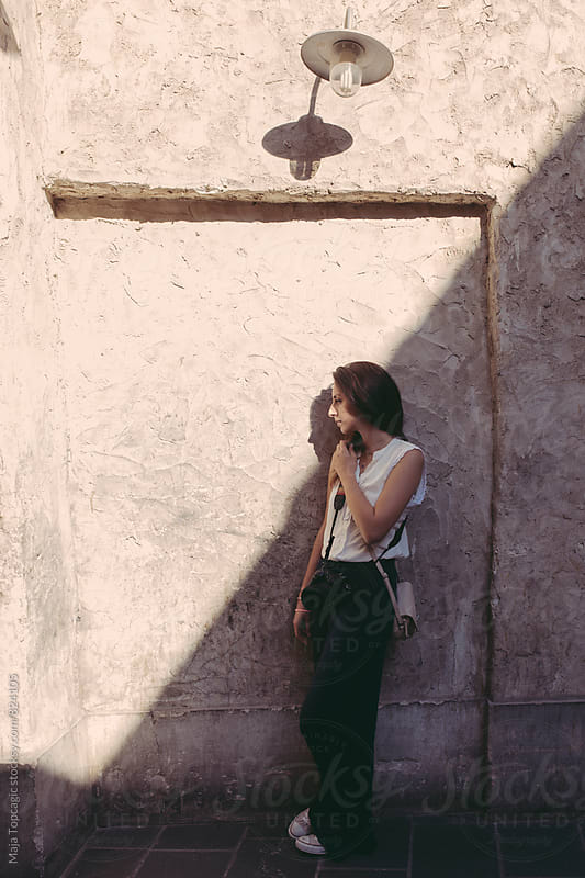 Young photographer in the sun against an old wall by Maja Topcagic for Stocksy United