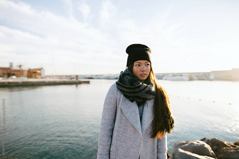 Portrait of an asian woman standing in front of the sea on winter. by BONNINSTUDIO for Stocksy United