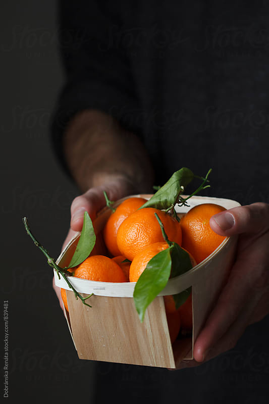 Man holding a basket of mandarin oranges by Dobránska Renáta for Stocksy United