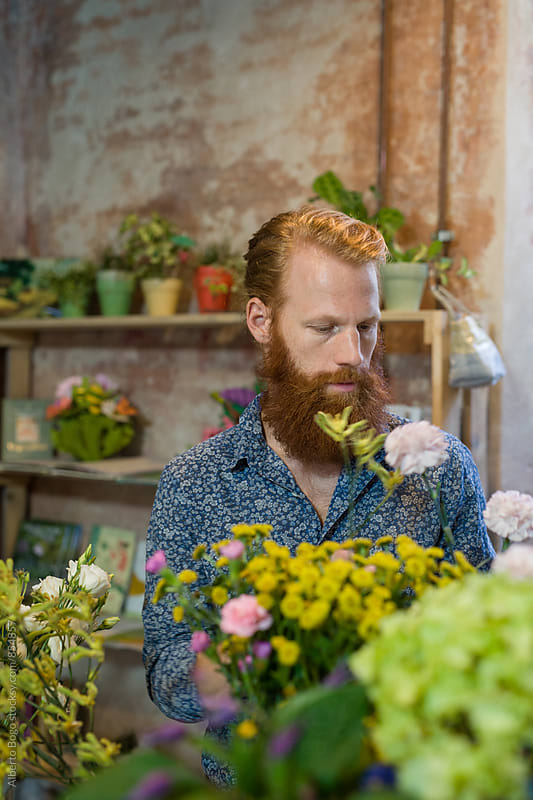 A florist arranging a flower bouquet in his shop by Alberto Bogo for Stocksy United