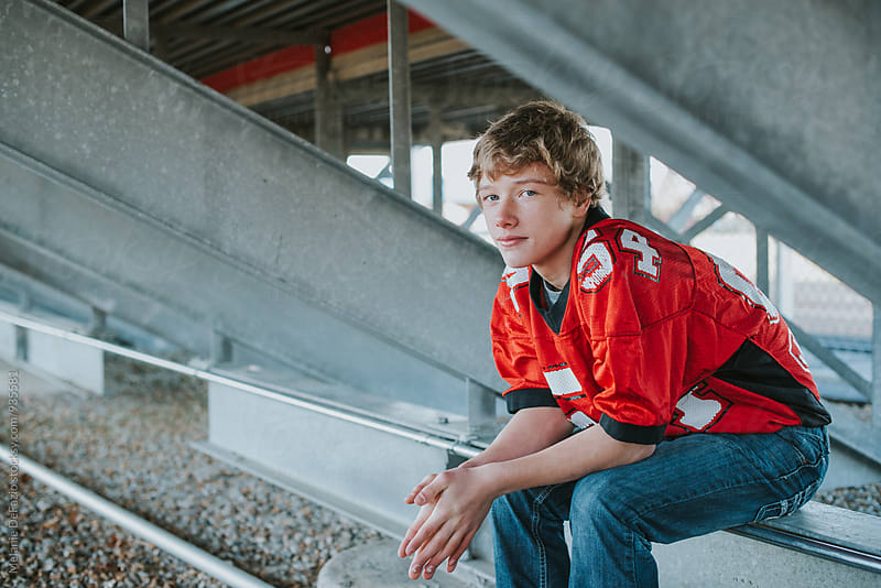 Teen football player by Melanie DeFazio for Stocksy United