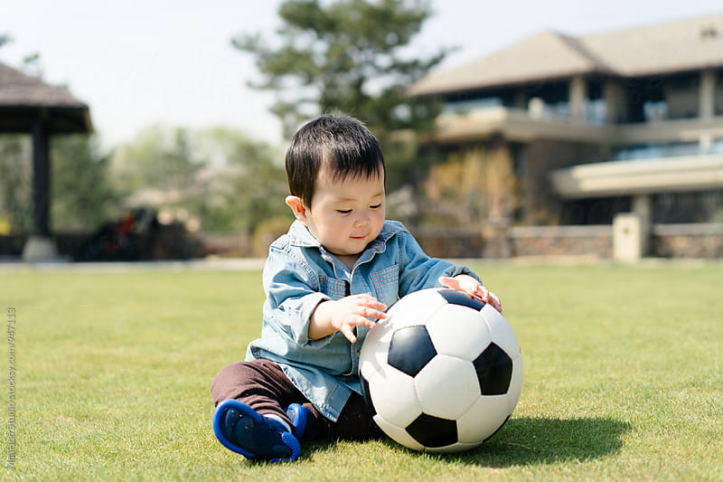 Baby boy playing football on grass by Maa Hoo for Stocksy United