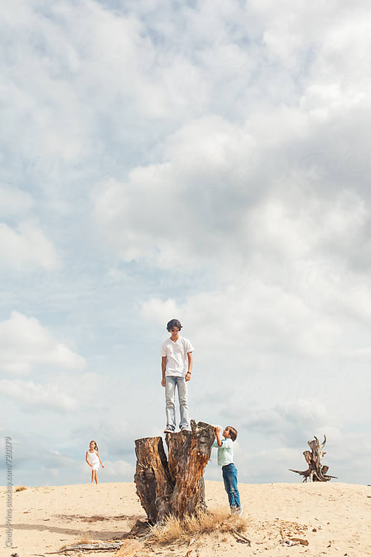 Teenage boy standing on a tree trunk and little kids roaming around by Cindy Prins for Stocksy United