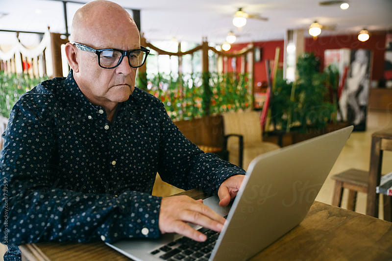 Senior businessman working with his laptop in a cafe restaurant by Inuk Studio for Stocksy United