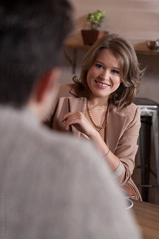 Well dressed young woman smiling and talking to a man in a trendy cafe by Ben Ryan for Stocksy United