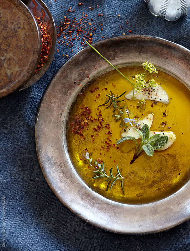 Pewter Bowl of olive oil and fresh and dried spices overhead on blue tablecloth by Sherry Heck for Stocksy United