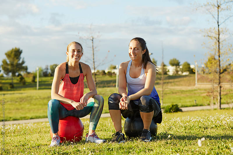 Happy Female Athletes Sitting On Medicine Balls by ALTO IMAGES for Stocksy United