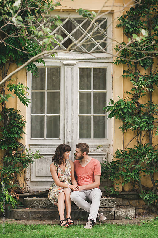 Couple sitting on the back porch of an old house by Irina Efremova for Stocksy United