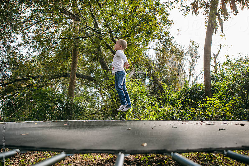 Boy jumping on trampoline by Stephen Morris for Stocksy United