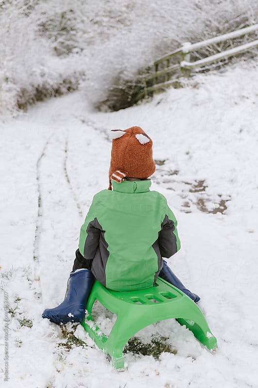 Boy ready to sledge down a hill by Rebecca Spencer for Stocksy United