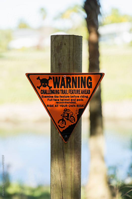 Warning sign on the side of a mountain biking trail by Adam Nixon for Stocksy United