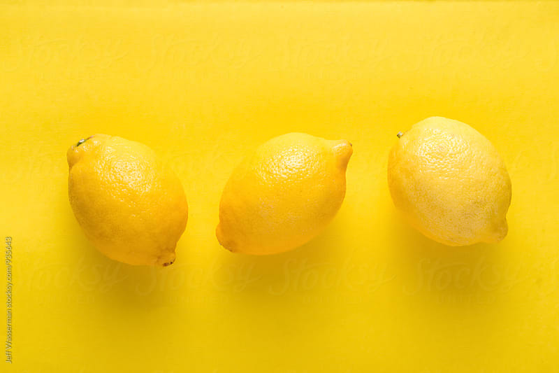Whole Lemons on Yellow Background by Jeff Wasserman for Stocksy United