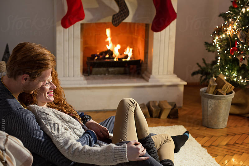 Ginger Couple Sitting by the Fireplace on Christmas Eve by Lumina for Stocksy United