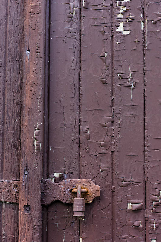 A rusty lock on the side of a brown, wooden barn. by Holly Clark for Stocksy United