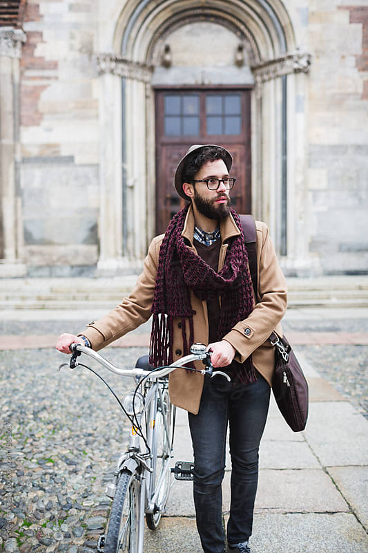 Young man holding a bicycle by michela ravasio for Stocksy United