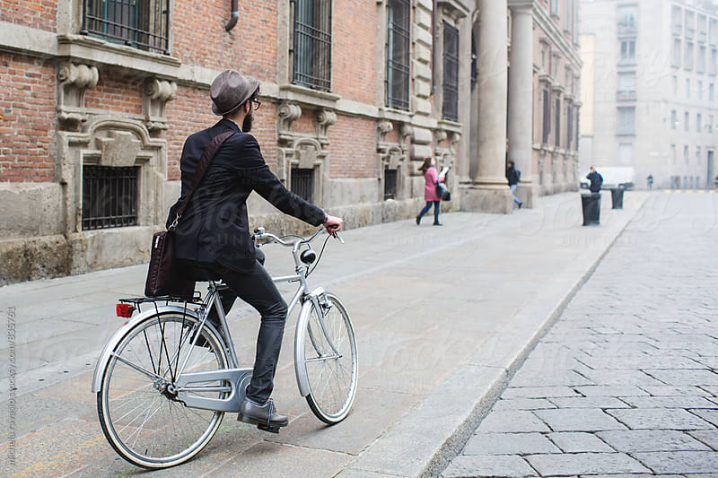 Man with hat riding his bike in the city center by michela ravasio for Stocksy United