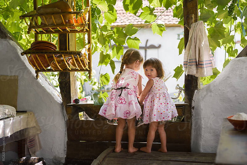 Two young sisters playing together in a rustic summer kitchen by RG&B Images for Stocksy United