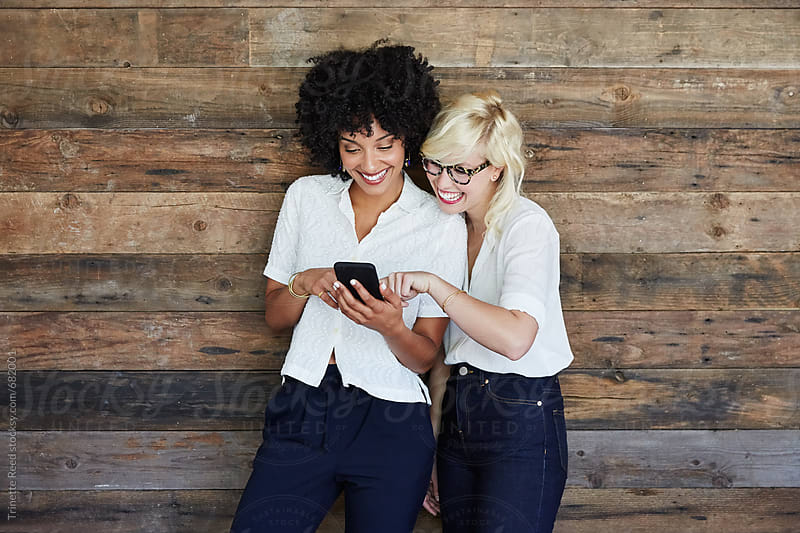 Portrait of millennial businesswomen laughing looking at cell phone by Trinette Reed for Stocksy United