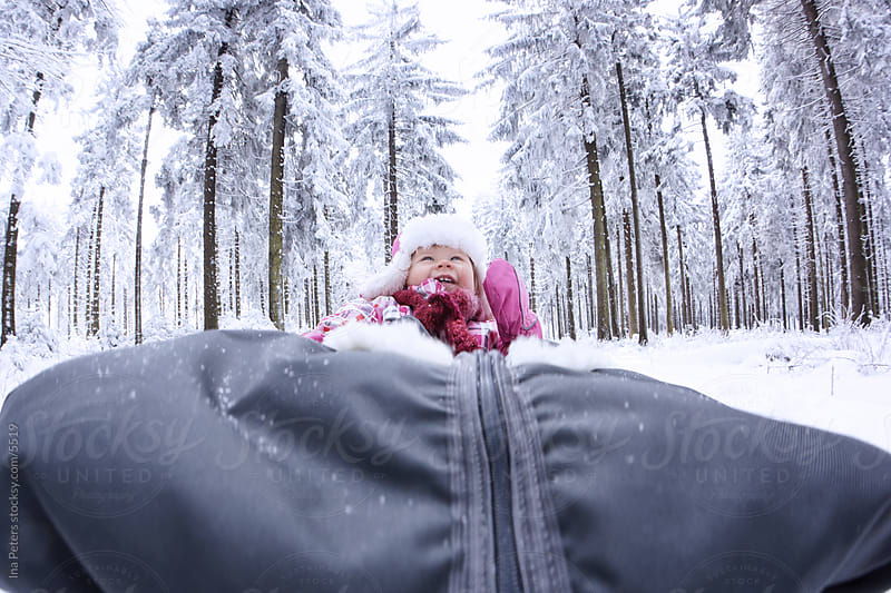 Little girl in a sleigh by Ina Peters for Stocksy United