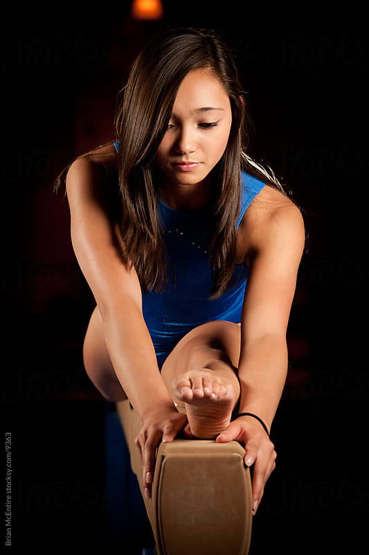Beautiful Asian Gymnast Stretches on Balance Beam by Brian McEntire for Stocksy United