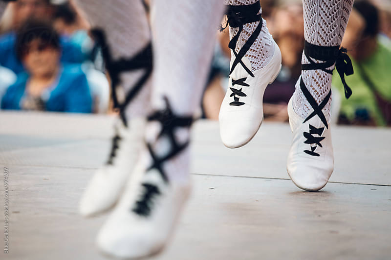 dancing the traditional Catalonian dance of the 'Sardana', wearing special white canvas and ribbon espadrilles. by Jordi Rulló for Stocksy United