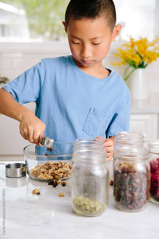 Healthy young boy preparing nuts and frutis by Curtis Kim for Stocksy United