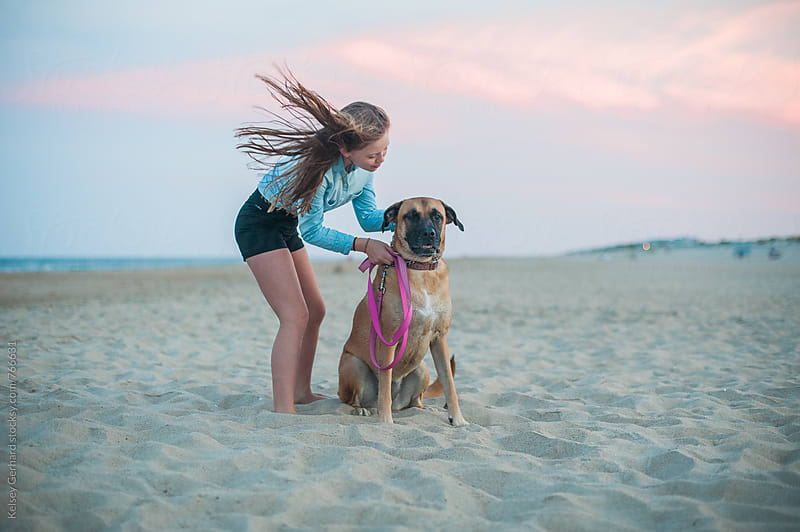 A tween girl comforts her large dog at the beach at sunset. by Kelsey Gerhard for Stocksy United