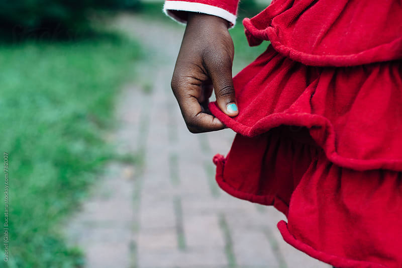Black girl holding her fluffy red dress by Gabriel (Gabi) Bucataru for Stocksy United