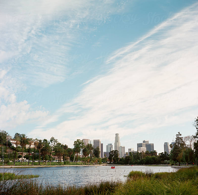 A Red Paddleboat in the Echo Park Lake with Downtown Los Angeles in the Background by Briana Morrison for Stocksy United