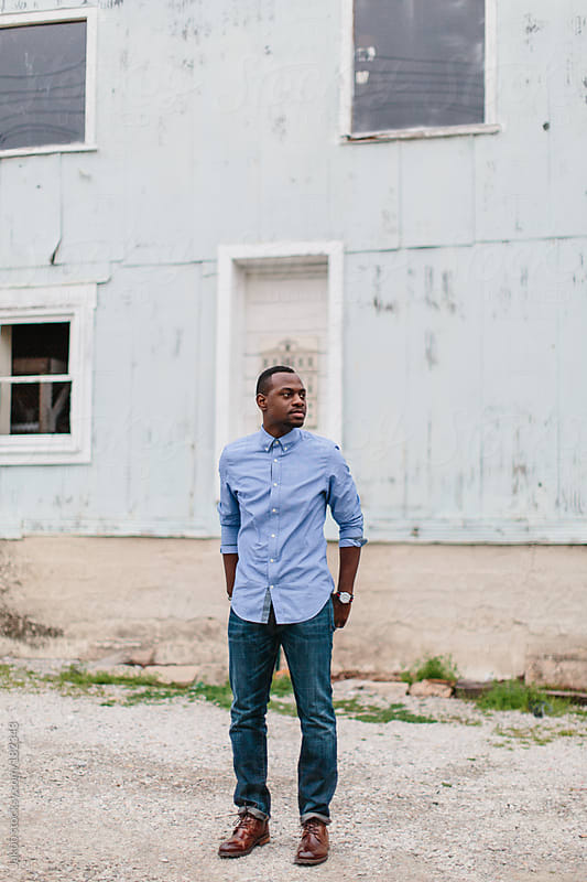 Portrait of a handsome and stylish african-american man in front of an abandoned building by Jakob for Stocksy United