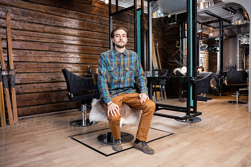 Confident Male Hairdresser Sitting On Chair At Beauty Salon by Tyler Olson for Stocksy United